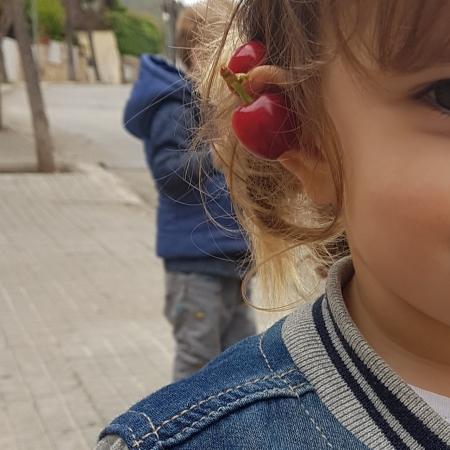 Cerezas en la oreja de una niña