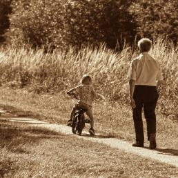 Avi i net amb bicicleta en un camí de camp