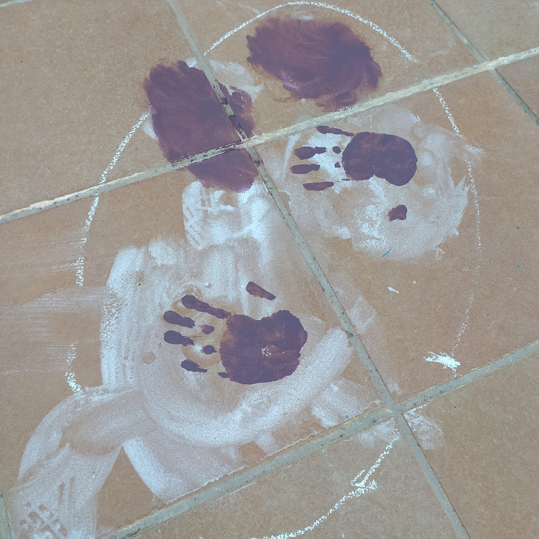 Manos morada estampadas en el suela de la terraza sobre blanco y dentro de círculo blanco de tiza. Dos formas moradas en el suelo sobre ellas.