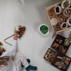 Pedres, botons de fusta, pals, nins, cons, retalls de fusta, escorça d'arbre... elements naturals classificats en cistells i una nena jugant