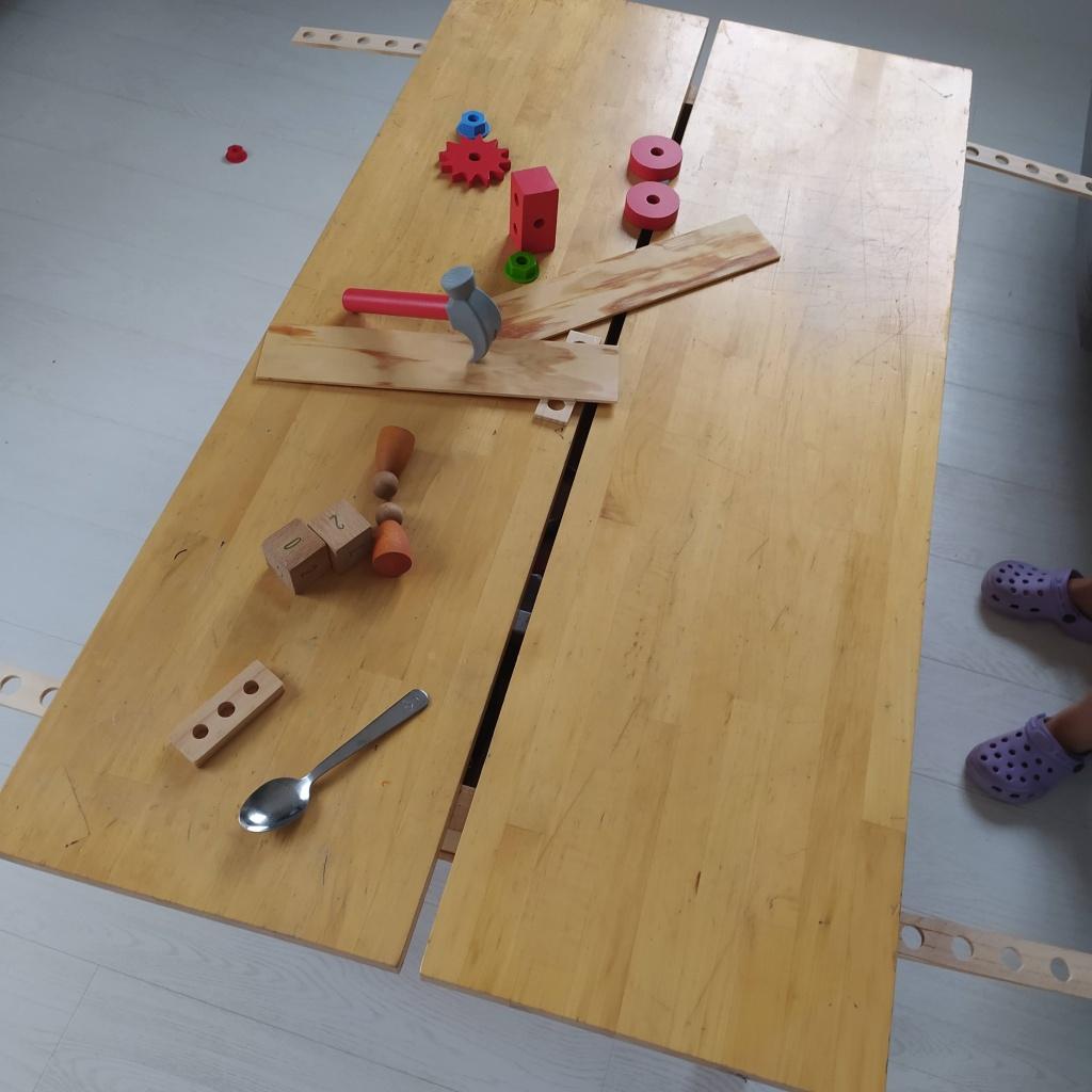 Mesa del café con herramientas, nins, piezas del banco de herramientas de juego de madera. cautro piezas alargadas en los bordes representan las alas del avión